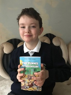 10-year-old Adam Rafael Holmes holding up his book, The Tunnel of Adventure